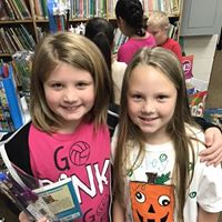 two student smiling while at book fair