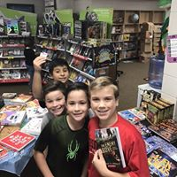 Four students showing off books purchased at the bookfair