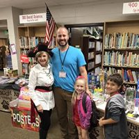 Parent volunteer, librarian, and students posing at bookfair