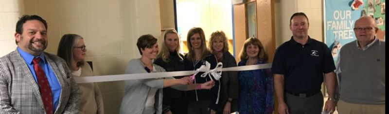 Board Members Cutting A Ribbon