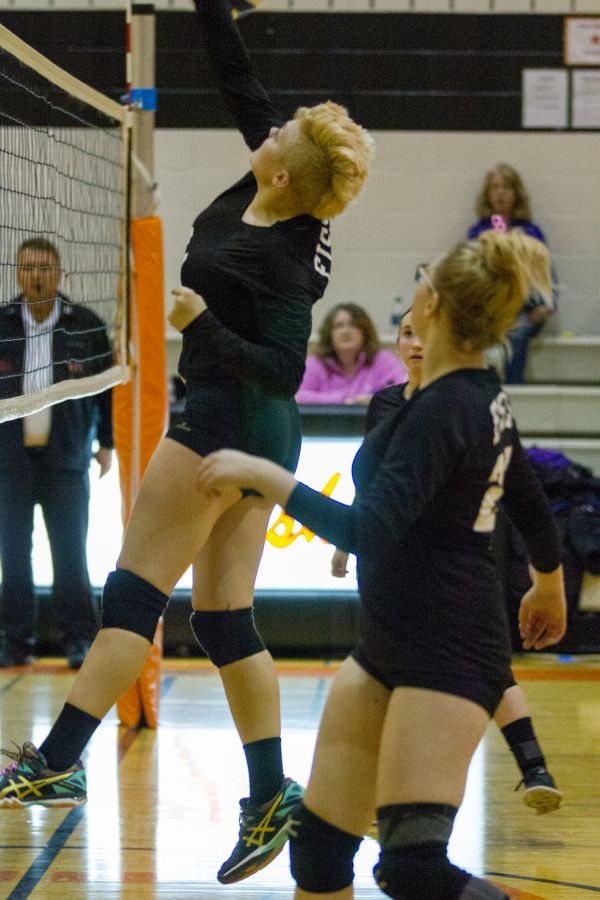 Fisher volleyball player spikes the ball
