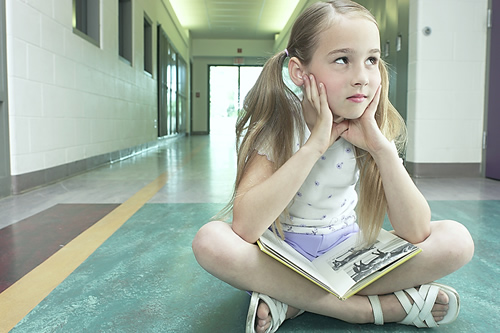 Girl sitting in hallway with a book.